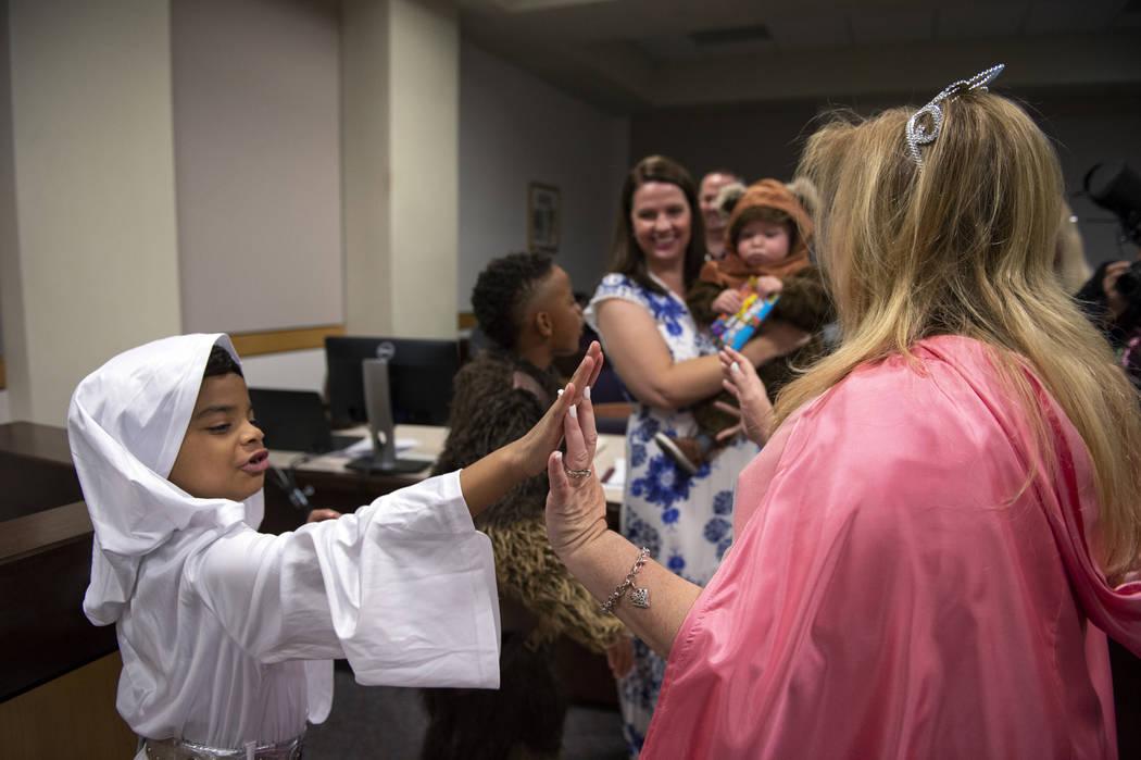 Jaelyn Elliott, de 7 años, choca las palmas con la Jueza de Familia, Cynthia Giuliani, después de haber jurado para su nuevo hermano adoptivo, Connor, de un año, en el Tribunal de Familia de La ...