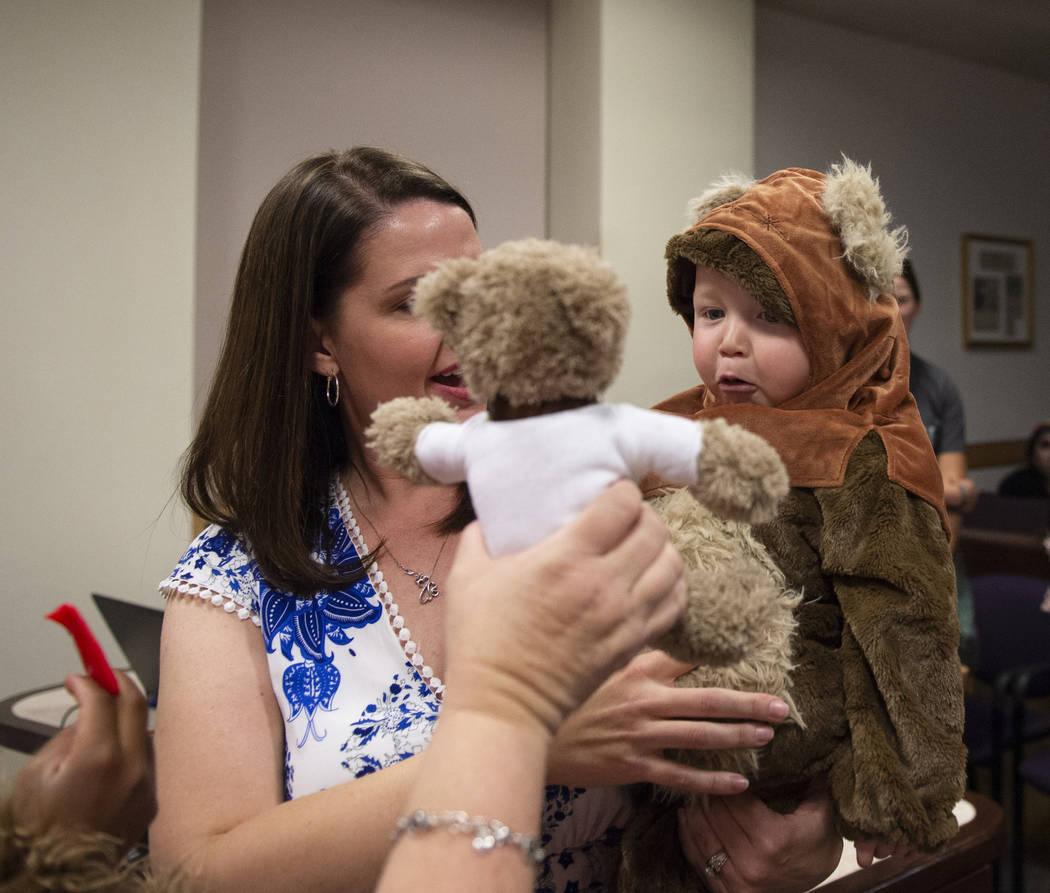 Julie Elliott sostiene al nuevo miembro de la familia, Connor de un año, mientras que la Jueza de Familia de la Corte de Distrito Cynthia Giuliani sostiene un oso de peluche en el Tribunal de Fam ...