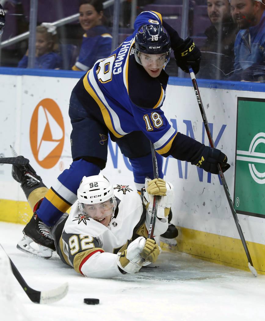 Tomas Nosek, de la República Checa, y Robert Thomas (18) de St. Louis Blues, de Vegas Golden Knights, mantienen la vista en el puck durante el primer período de un juego de hockey de la NHL el j ...
