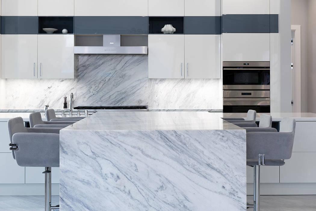 La cocina cuenta con una gran isla de mármol con borde de cascada y asientos de bar. (Steve Morgan)