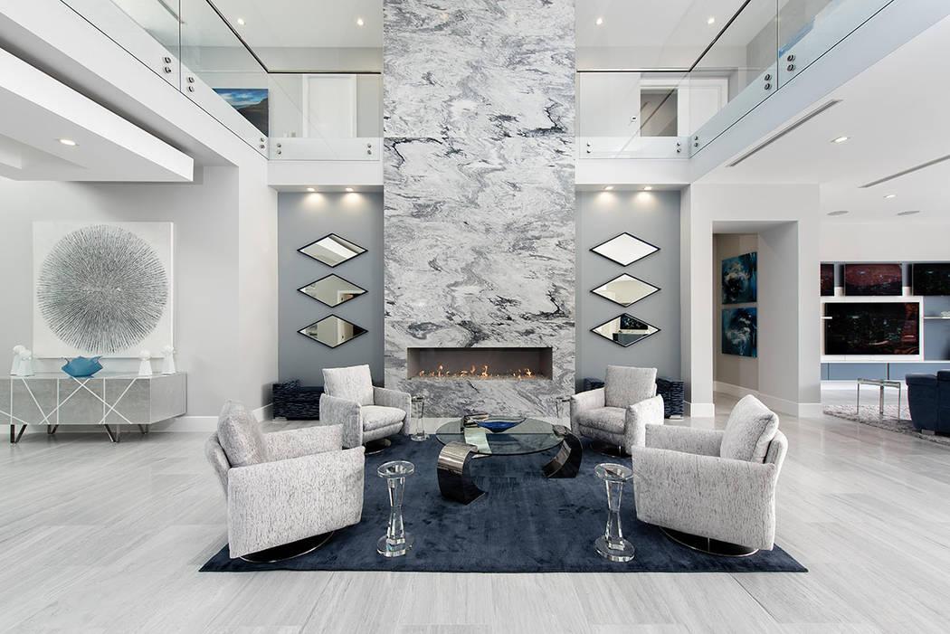 La chimenea encerrada en mármol gris del piso al techo de la gran sala, enmarcada por una serie de espejos en forma de diamante, sirve como un punto focal impresionante para la sala de estar prin ...