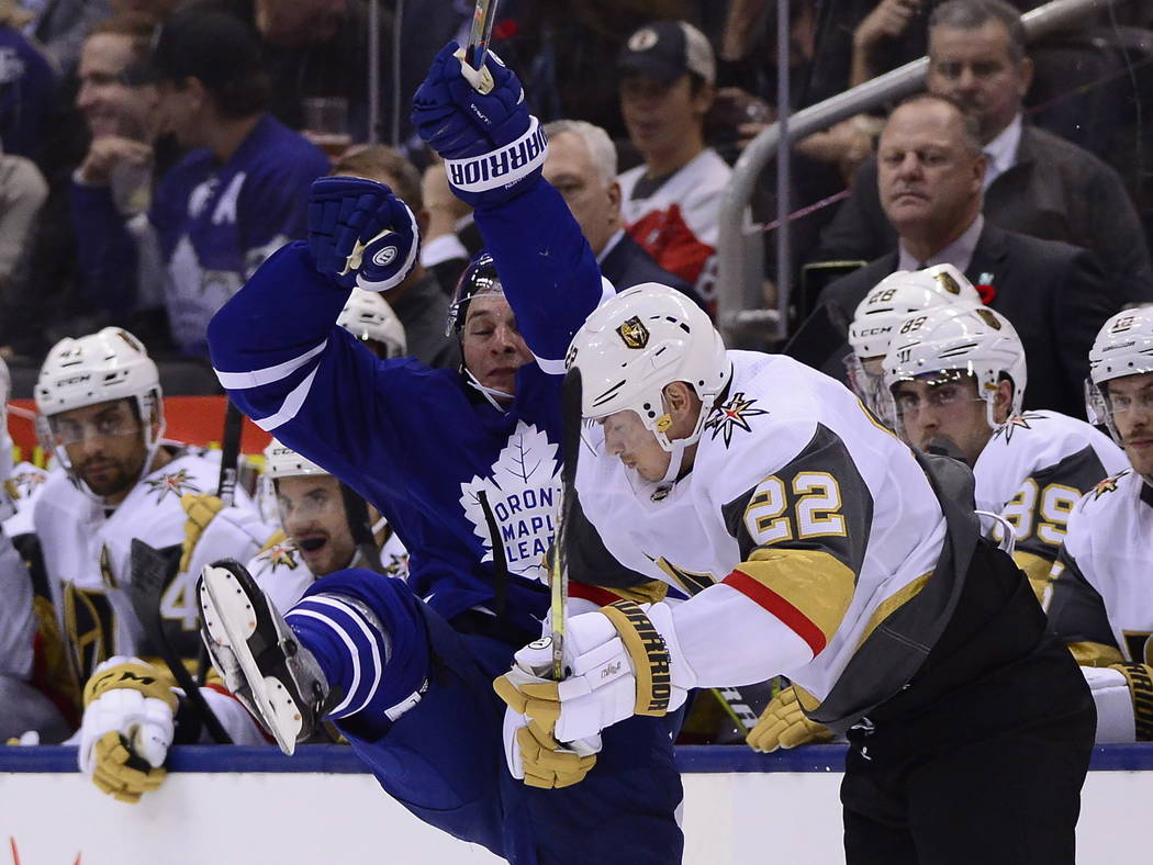 El defensa Morgan Rielly (44) de los Toronto Maple Leafs es golpeado en el hielo por el defensa Nick Holden (22) de los Golden Knights de Vegas durante el segundo período de un juego de hockey de ...