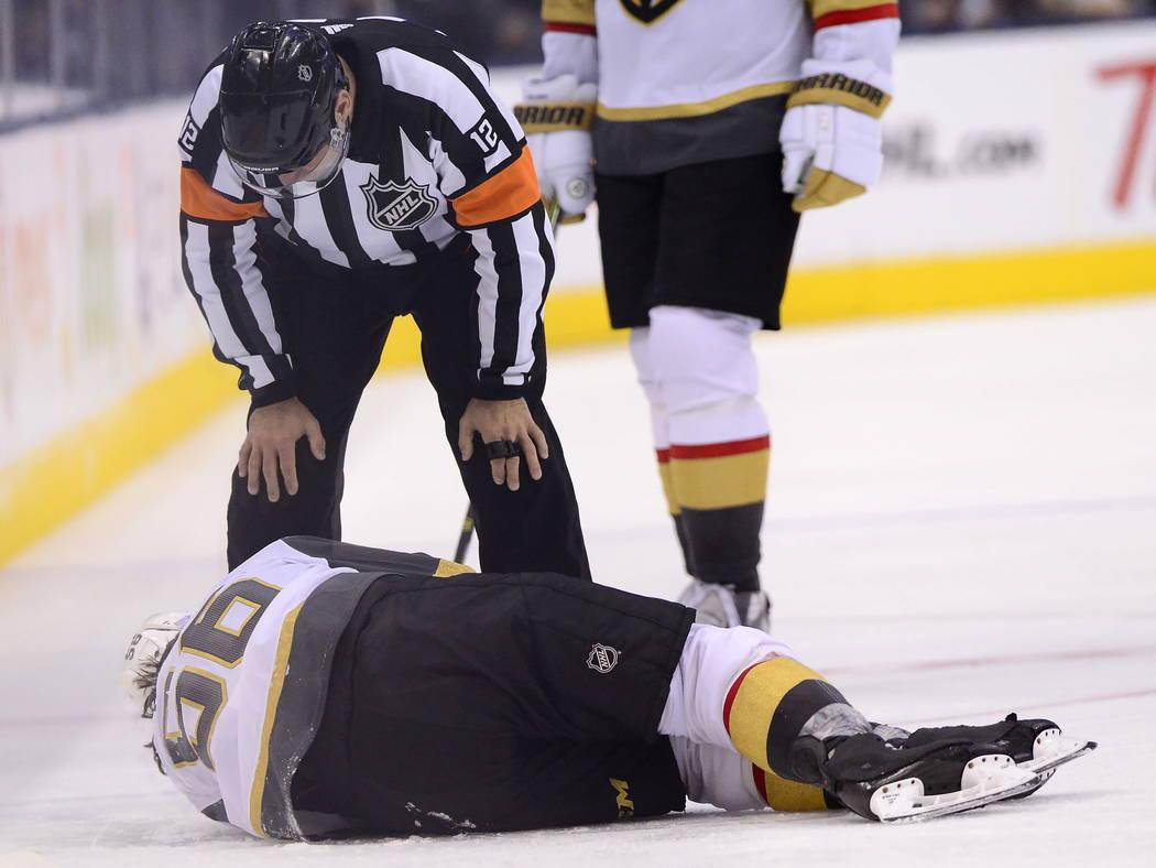 El centro de los Golden Knights de Vegas, Erik Haula (56), se recuesta en el hielo después de recibir un golpe en las tablas durante el tercer período de un juego de hockey de la NHL contra los ...