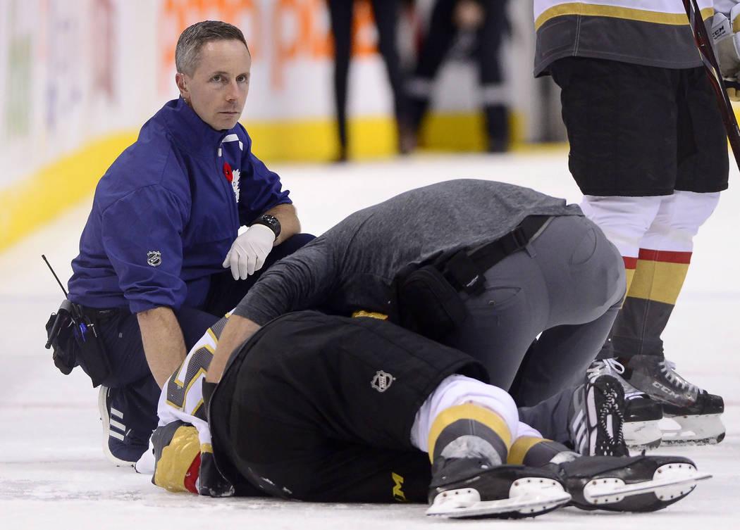 Un entrenador asiste al centro de los Vegas Golden Knights, Erik Haula (56), quien recibió un golpe en las tablas durante el tercer período de un juego de hockey de la NHL contra los Toronto Map ...