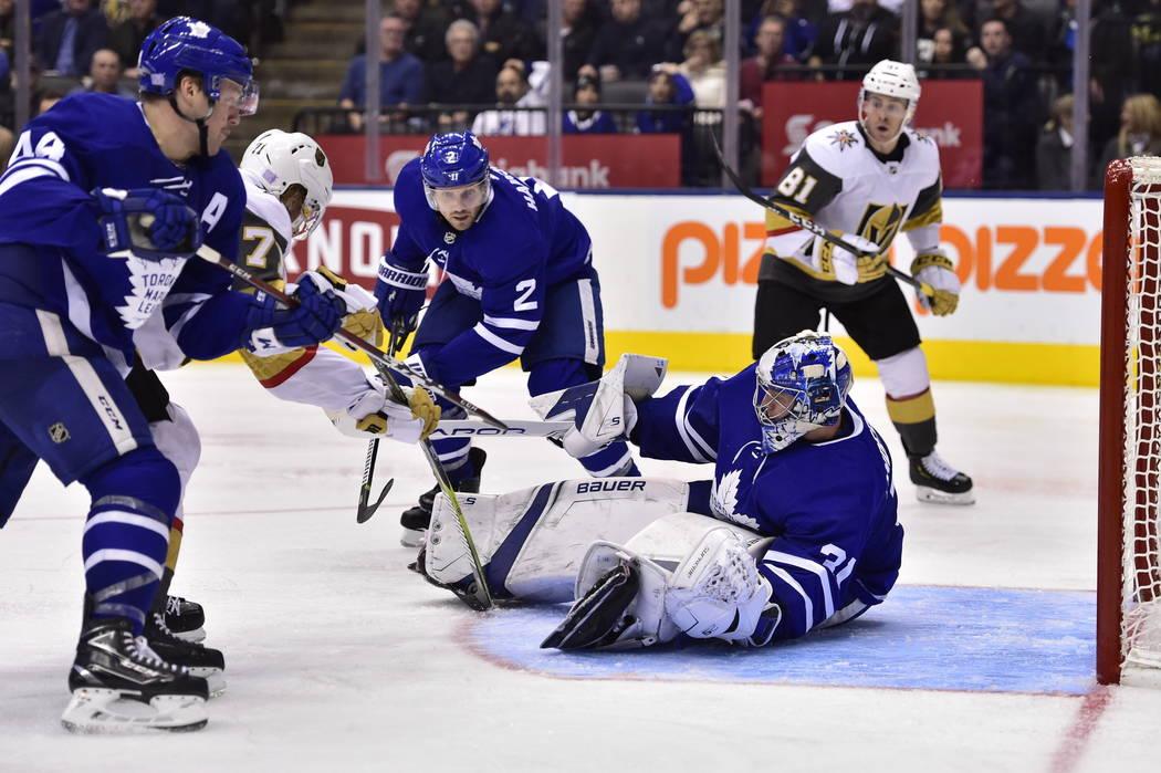 El centro de los Golden Knights, William Karlsson (71) y el defensa de los Toronto Maple Leafs, Morgan Rielly (44) y Ron Hainsey (2) luchan frente al portero Frederik Andersen (31) de los Maple Le ...