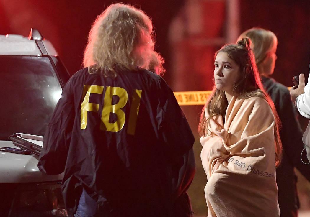Un agente del FBI habla con un testigo potencial mientras se encuentran cerca de la escena el jueves 8 de noviembre de 2018, en Thousand Oaks, California, donde un hombre armado abrió fuego el mi ...