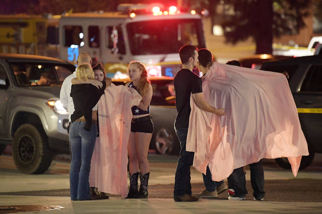 Las personas se consuelan mutuamente mientras permanecen de pie cerca de la escena el jueves 8 de noviembre de 2018, en Thousand Oaks, California, donde un hombre armado abrió fuego el miércoles ...