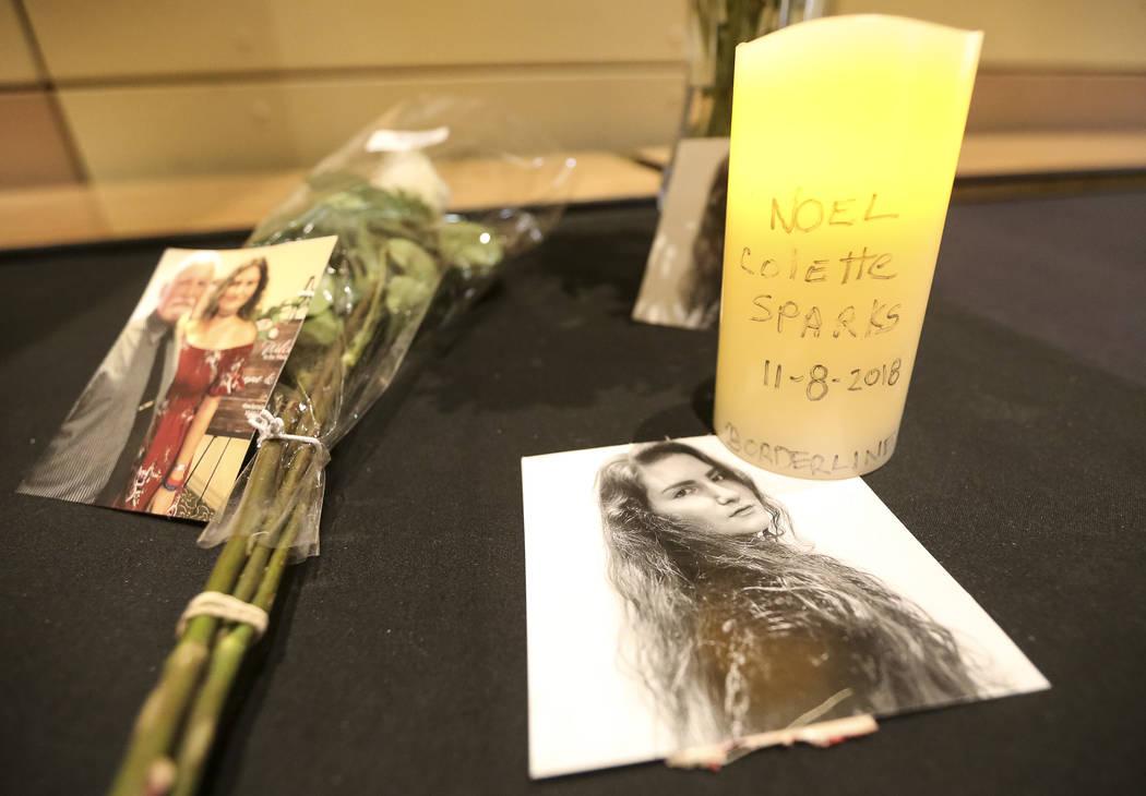 Fotos que recuerdan a la víctima del tiroteo, Noel Colette Sparks, se sientan entre un ramo de flores y una vela encendida durante un velorio para las víctimas del tiroteo masivo Borderline Bar ...