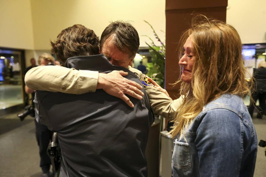 El jefe de la policía de Thousand Oaks, Tim Hagel, centro, es consolado por los residentes de la ciudad Jim Friedl, a la izquierda, y Christina Duffy, durante un velorio para las víctimas del ti ...