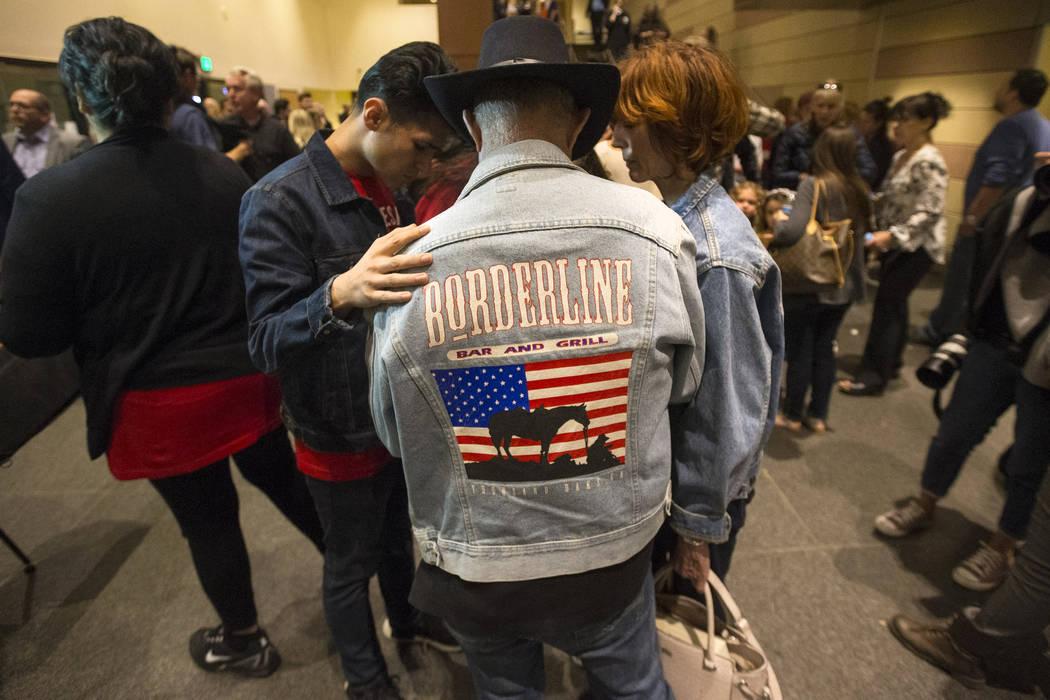 Eric Blanco, segundo a la izquierda, se reúne en oración con Cliff y Kathy Housego durante un velorio para las víctimas de la masacre de Borderline Bar and Grill en Thousand Oaks, California, e ...