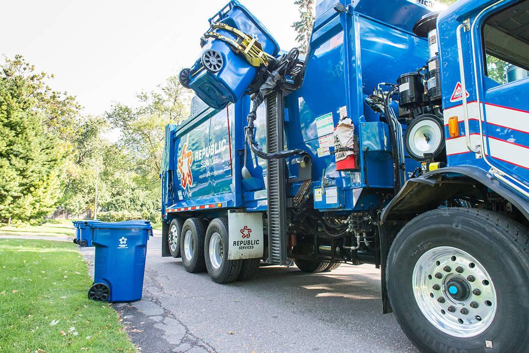 Un camión de Republic Services levanta un contenedor de basura residencial. Al lado otro contenedor con materiales reciclables espera por otro camión. Foto Cortesía Republic Services.