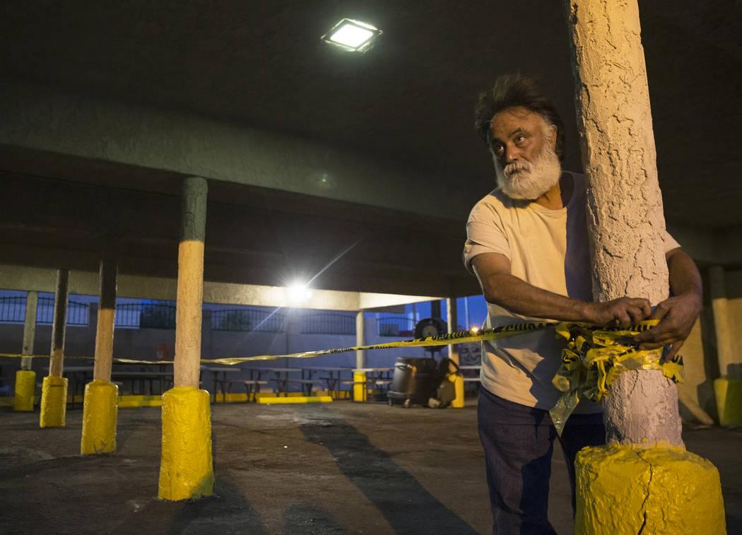 Leo Afshar, un miembro del personal del Programa de Mejoramiento de la Salud de la Comunidad del Sur de Nevada, prepara el área para dormir en el patio para personas sin hogar de la ciudad de Las ...