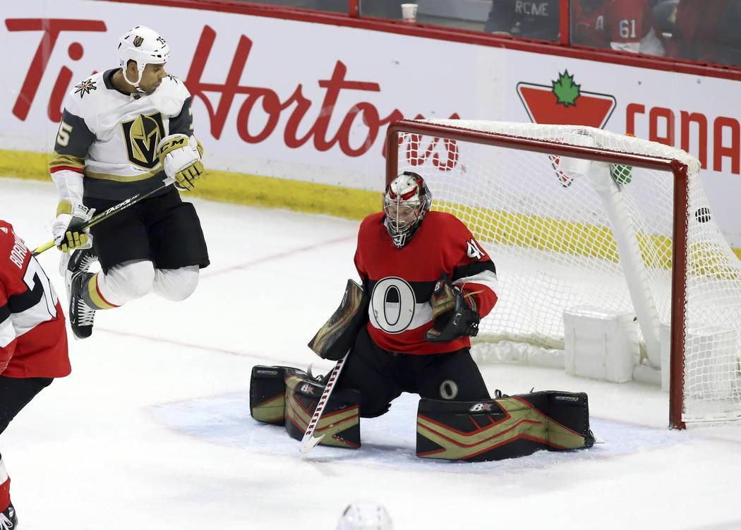 El puck pasa por el portero de los Senators de Ottawa, Craig Anderson (41), cuando es examinado por el alero derecho de los Golden Knights de Vegas, Ryan Reaves (75), en un tiro del defensa de los ...