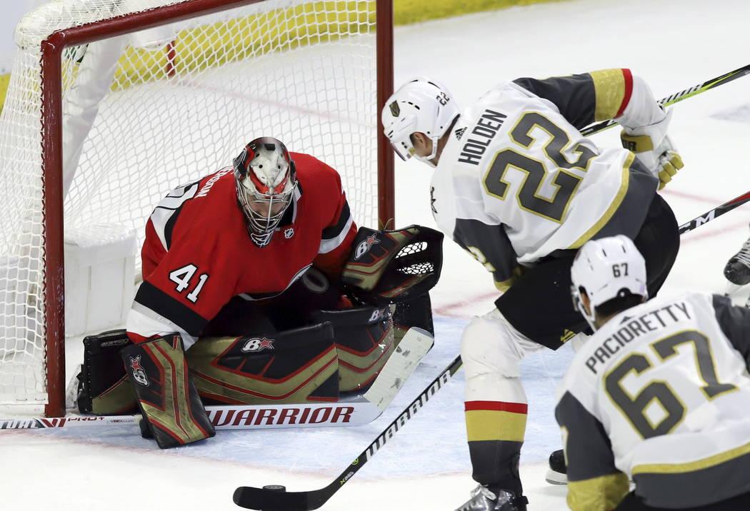 El defensa Nick Holden (22) de los Golden Knights de Vegas anota al portero Craig Anderson (41) de los Ottawa Senators mientras que el alero izquierdo de los Golden Knights de Vegas, Max Paciorett ...