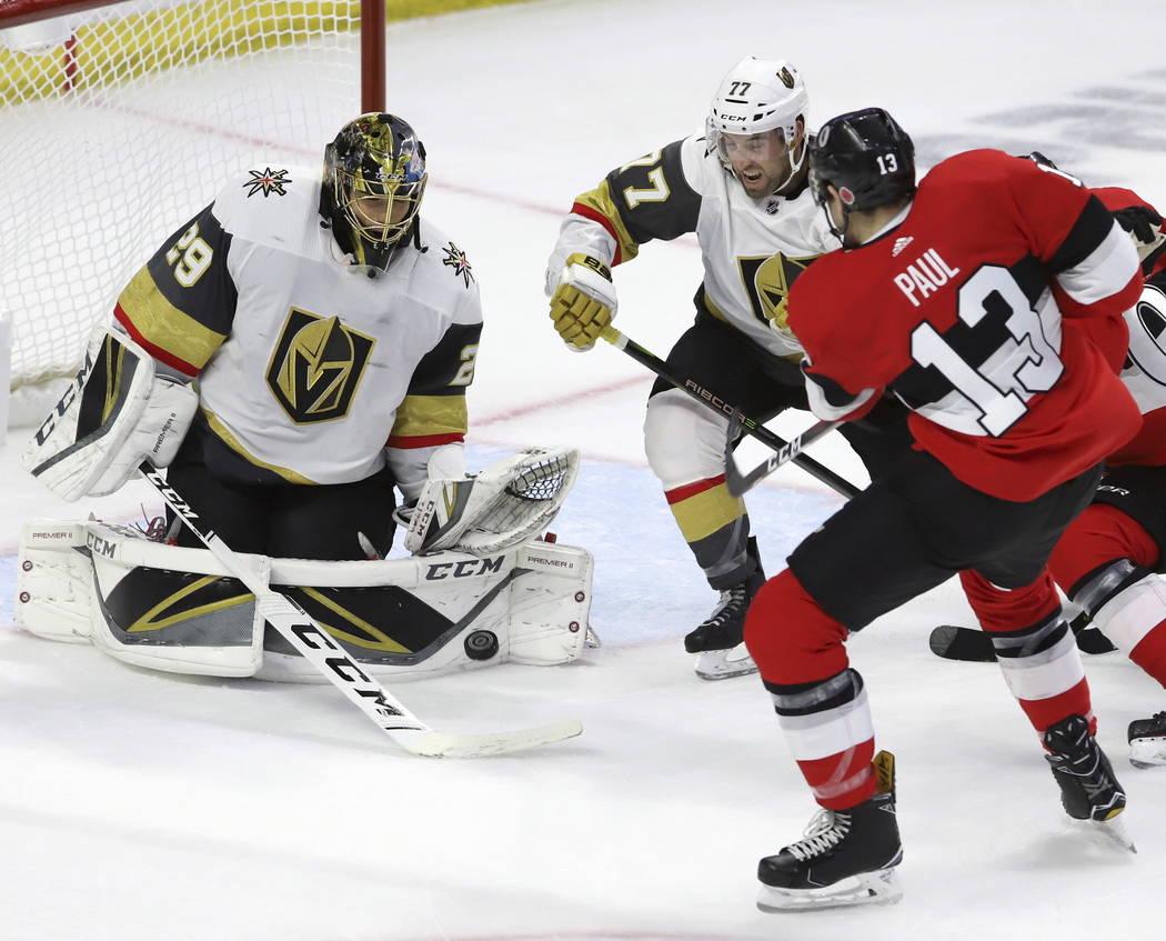 Marc-André Fleury (29), portero de los Golden Knights de Vegas, hace una anotación con el alero izquierdo de los senadores de Ottawa, Nick Paul (13), mientras el defensa de los Golden Knights de ...
