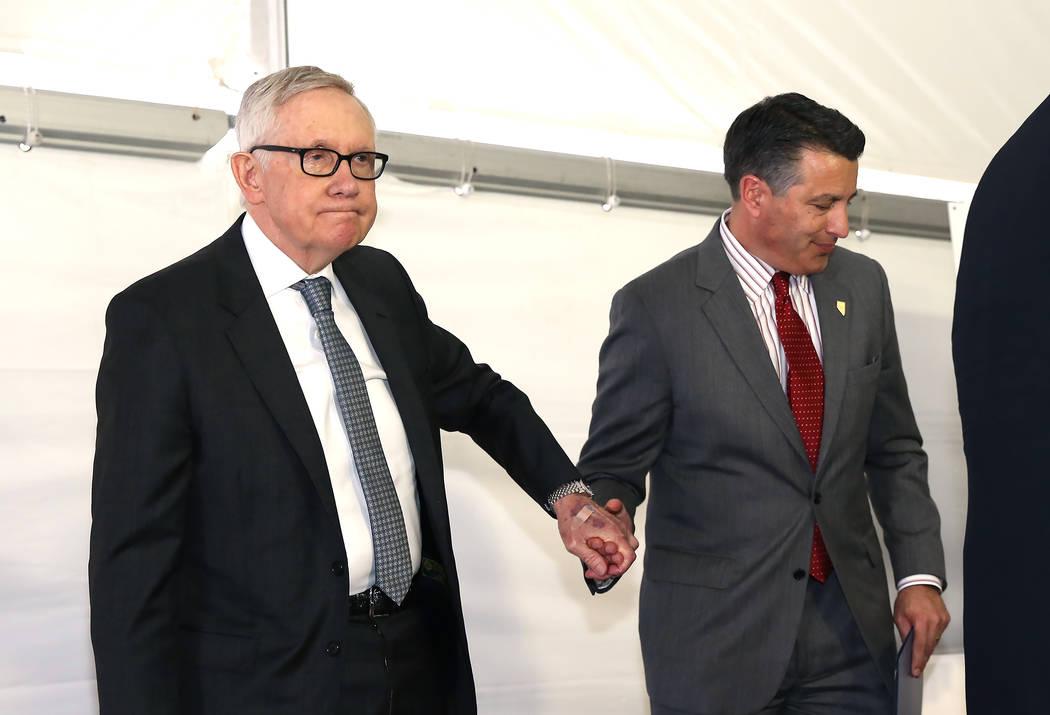 El gobernador Brian Sandoval, a la derecha, le da la mano al senador estadounidense Harry Reid, demócrata por Nevada, después de pronunciar un discurso durante la gran ceremonia de inauguración ...