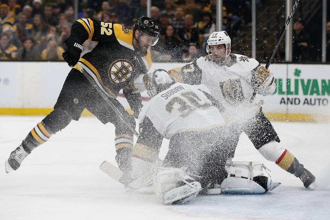 Malcolm Subban (30) de los Golden Knights de Las Vegas detiene el puck cuando Sean Kuraly (52) de los Boston Bruins busca un rebote durante el segundo período de un juego de hockey de la NHL en B ...