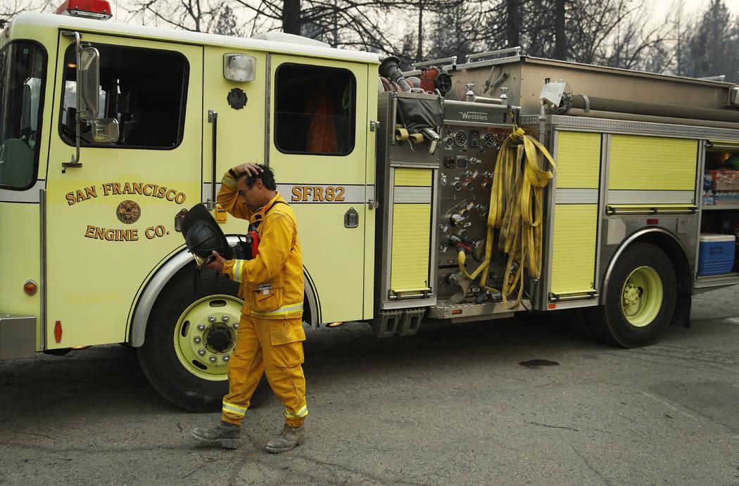 Un bombero descansa después de ayudar a encontrar restos humanos encontrados en una casa incendiada en el Camp Fire, el domingo 11 de noviembre de 2018, en Paradise, California (Foto AP / John Lo ...