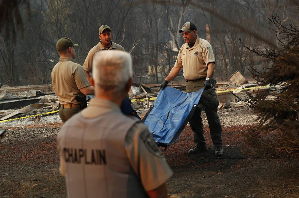 El oficial forense Justin Sponhaltz, a la derecha, de la Oficina del Alguacil del Condado de Mariposa, lleva una bolsa con restos humanos encontrados en una casa incendiada en el Camp Fire, el dom ...