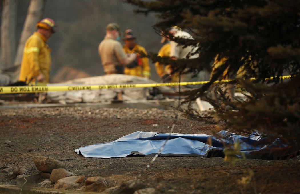 Una bolsa con restos humanos se encuentra en el suelo mientras los funcionarios continúan buscando en una casa incendiada en el Camp Fire, el domingo 11 de noviembre de 2018, en Paradise, Califor ...