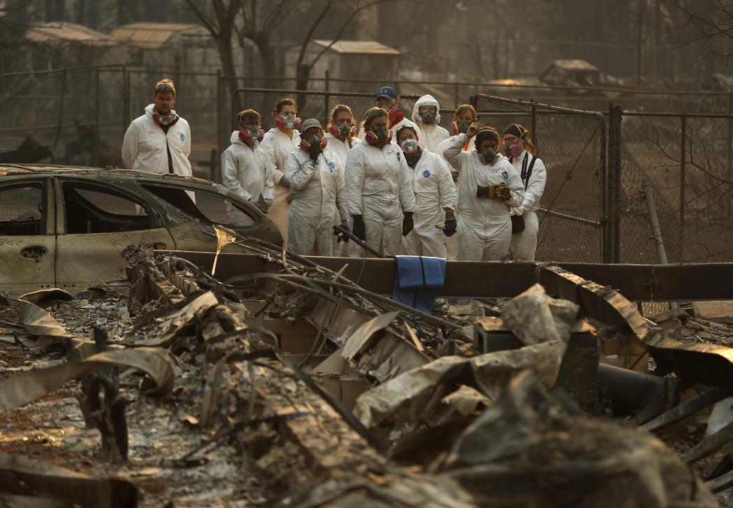 Estudiantes de antropología observan cómo los restos humanos se recuperan de una casa quemada en el Camp Fire, el domingo 11 de noviembre de 2018, en Paradise, California (Foto AP / John Locher)