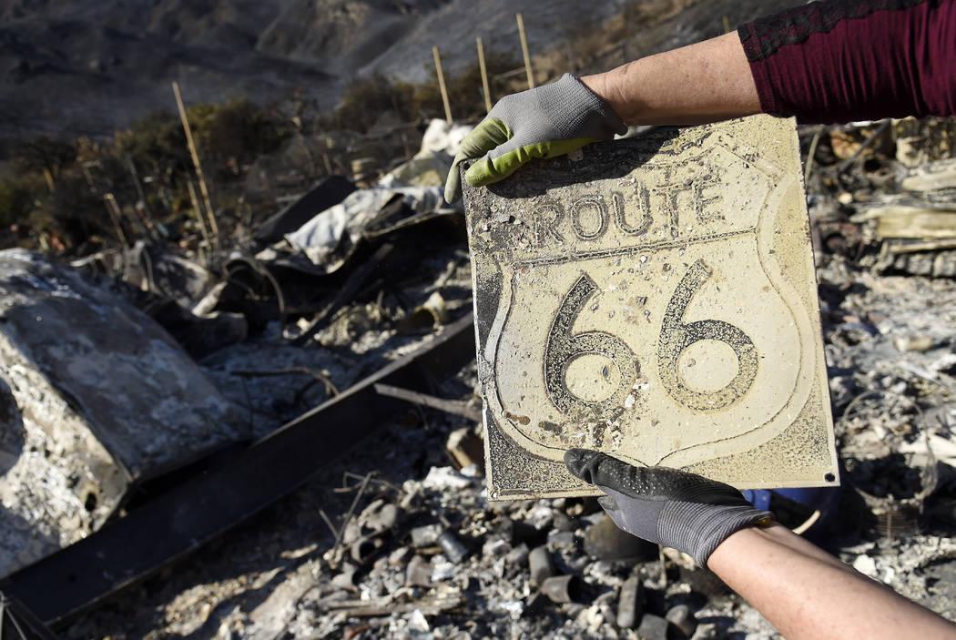 Donna Phillips muestra un cartel de la Ruta 66 carbonizado que encontró entre las posesiones de su amiga Marsha Maus, el domingo 11 de noviembre de 2018, después de que los incendios forestales ...