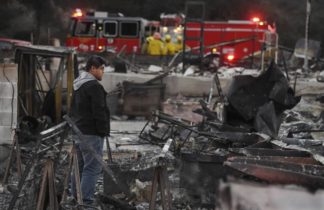 Ricky Alvarado mira los restos carbonizados de su hogar en el parque de casas móviles de Seminole Springs, el domingo 11 de noviembre de 2018, luego de que el vecindario fue devastado por incendi ...