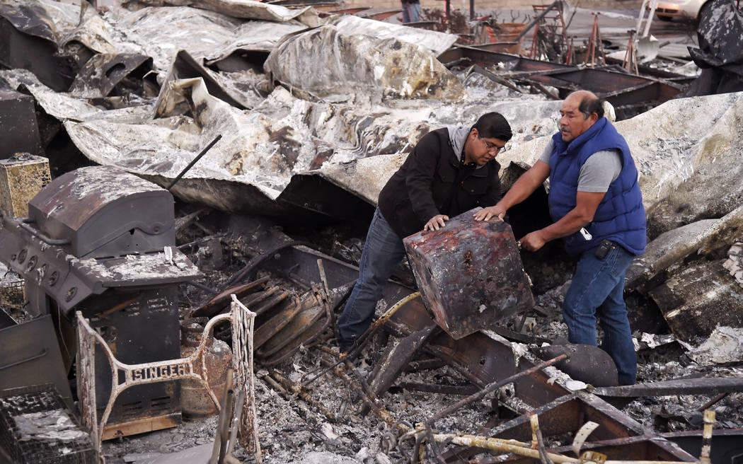 Santos Alvarado, a la derecha, y su hijo Ricky recuperan una caja de seguridad de su casa destruida en el parque de casas móviles de Seminole Springs, el domingo 11 de noviembre de 2018, luego de ...