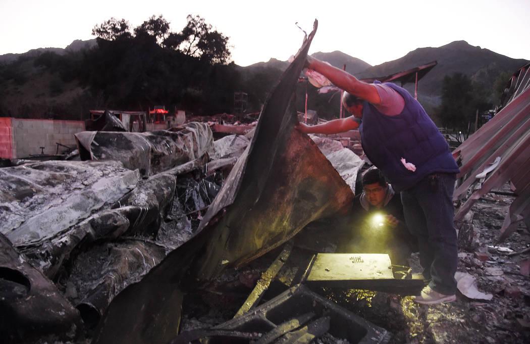 Santos Alvarado, a la derecha, y su hijo Ricky buscan sus pertenencias en su casa destruida en el parque de casas móviles Seminole Springs, el domingo 11 de noviembre de 2018, luego de los devast ...