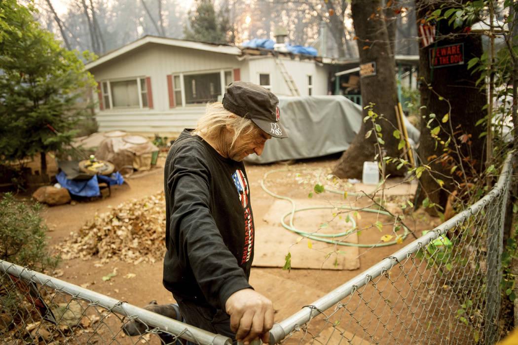 Jimmy Clements, que se quedó en su casa mientras el incendio en el campo arrasaba en Paradise, California, se apoya contra su cerca, el domingo 11 de noviembre de 2018. Clements, cuya casa se enc ...
