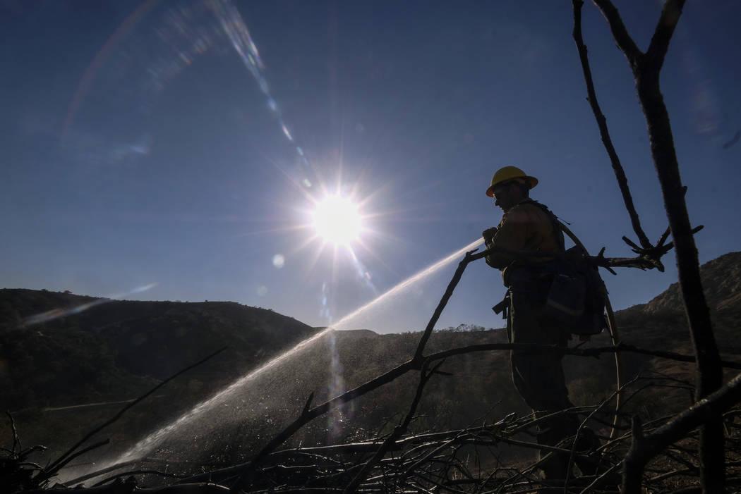 Un bombero rocía agua en los puntos calientes restantes en un área en West Hills, California, el domingo 11 de noviembre de 2018. (Foto AP / Ringo H.W. Chiu)