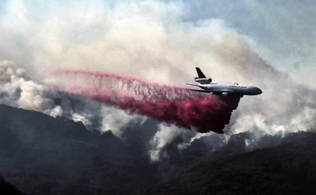 Un DC-10 de extinción de incendios provoca una caída ignífuga sobre un incendio forestal en las montañas cerca de Malibu Canyon Road en Malibu, California, el domingo 11 de noviembre de 2018. ...