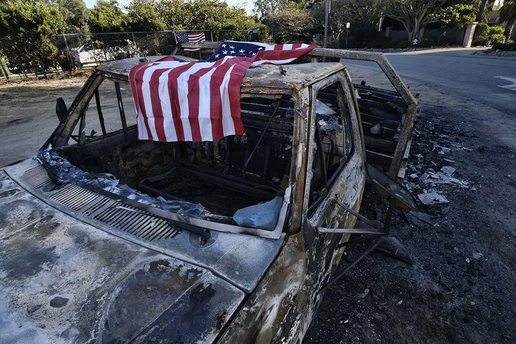 Una bandera estadounidense cubre los restos carbonizados de una vieja camioneta que ingresa a Point Dume a lo largo de la autopista de la costa del Pacífico en Malibu, California, el domingo 11 d ...