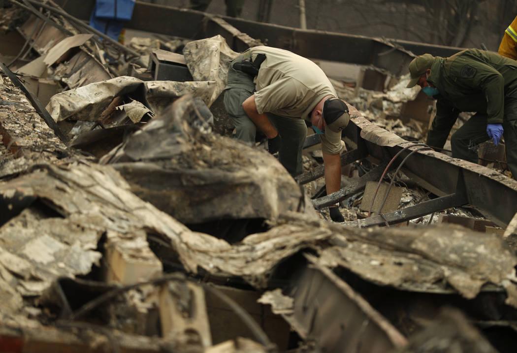 El oficial forense Justin Sponhaltz, de la Oficina del Sheriff del Condado de Mariposa, recupera los restos humanos encontrados en una casa destruida por el Camp Fire, el domingo 11 de noviembre d ...