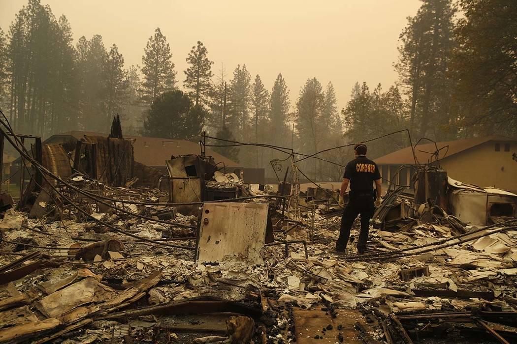 Un miembro de la oficina del forense del Condado de Sacramento busca restos humanos en los escombros de una casa quemada en el Camp Fire, el lunes 12 de noviembre de 2018, en Paradise, California ...