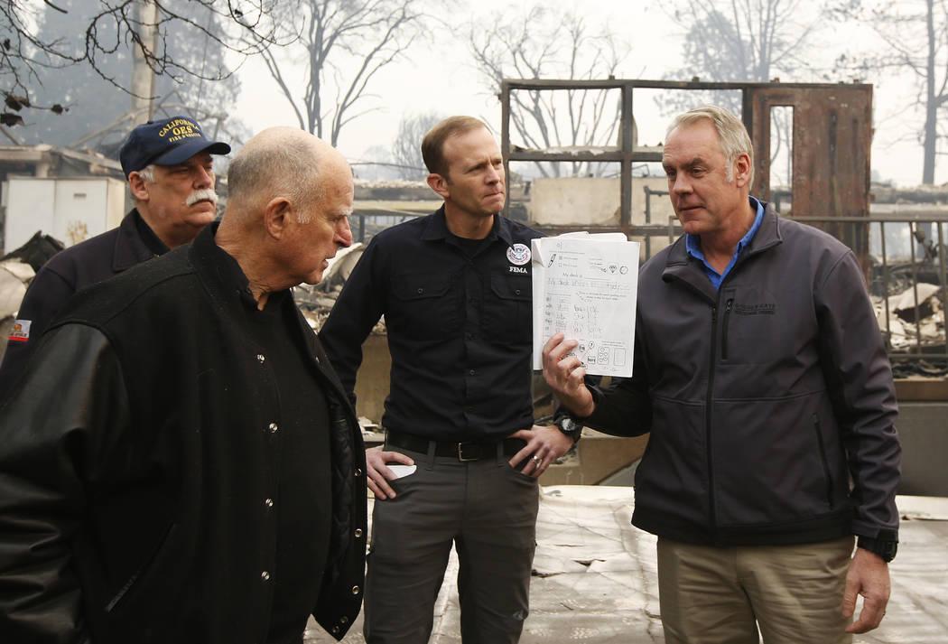 El gobernador de California, Jerry Brown, segundo a la izquierda, mira el cuaderno de un estudiante, mostrado por el secretario del Interior Ryan Zinke, que se encontró durante un recorrido por l ...