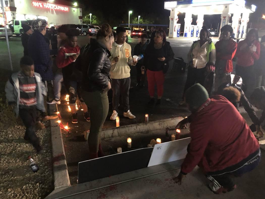 Sydney Harris, de 33 años, se encuentra más cerca del frente de carteles que recuerdan a su hijo, LaMadre Harris, de 16 años, después de un velorio el miércoles por la noche. El joven de 16 a ...