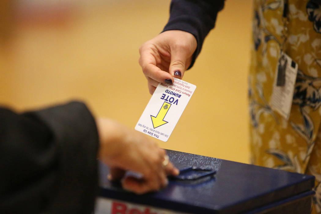 Un votante devuelve una tarjeta de votación después de depositar sus boletas electorales en un colegio electoral en la escuela histórica de Fifth Street en Las Vegas, el martes 6 de noviembre d ...