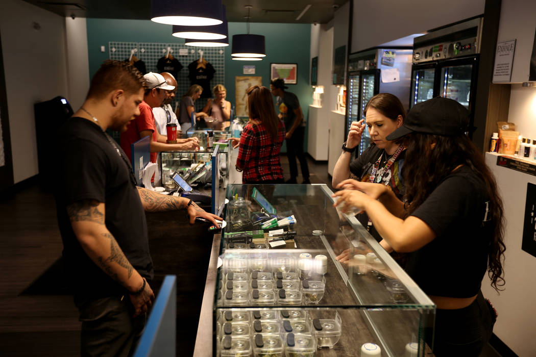 Eddie Medina de Seattle revisa el producto con Lindsay Steel, derecha, y Alyssa Jusino en el dispensario de marihuana Exhale Nevada en Las Vegas el jueves 28 de junio de 2018. K.M. Cannon Las Vega ...