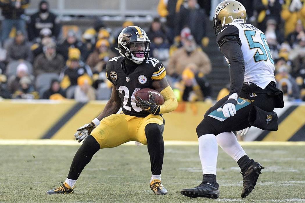 El corredor de los Pittsburgh Steelers, Le'Veon Bell (26), intenta superar al alero defensivo de los Jacksonville Jaguars, Dante Fowler (56). durante la segunda mitad de un partido de playoffs de ...
