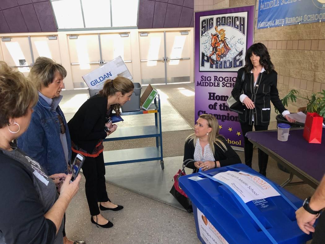 Anna Robbins (tercera desde la derecha), directora de la Fundación Conservar Viva la Memoria, supervisa la entrega del cargamento con monedas colectadas en la escuela secundaria Rogich. Viernes 1 ...