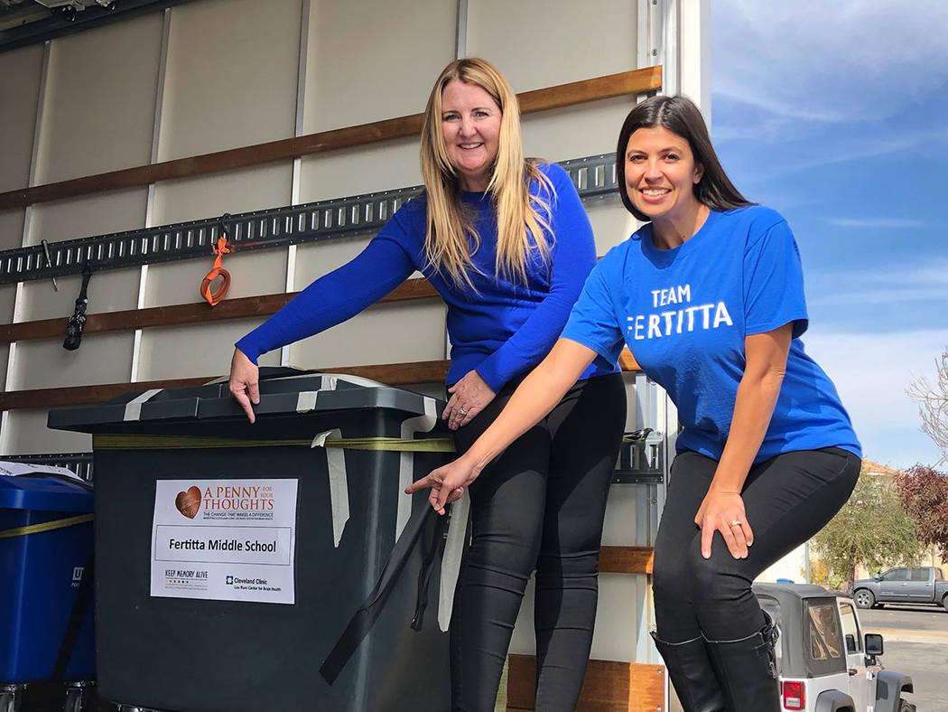 """Cailin Ellis (izquierda), directora de la escuela secundaria Fertitta, y la decana Melanie Boyer posan junto a la caja con las monedas colectadas por los alumnos para apoyar a la campaña """"Un pe ..."""