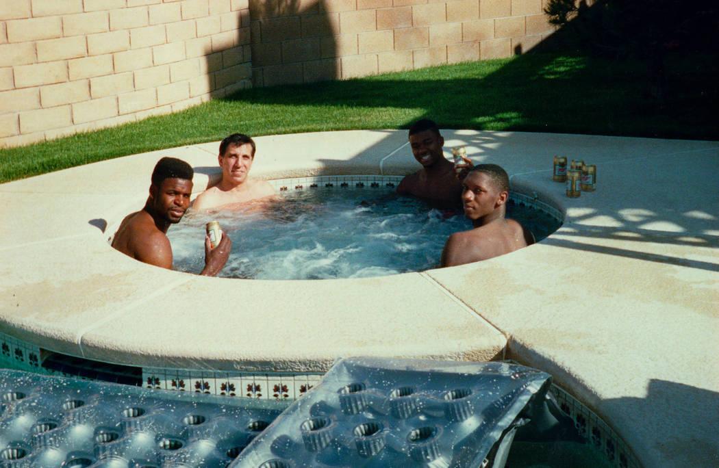 Los jugadores de baloncesto de la UNLV, Moses Scurry, a la izquierda, Anderson Hunt, segundo a la derecha y David Butler, a la derecha, se sientan en un jacuzzi con el conocido apañador de deport ...