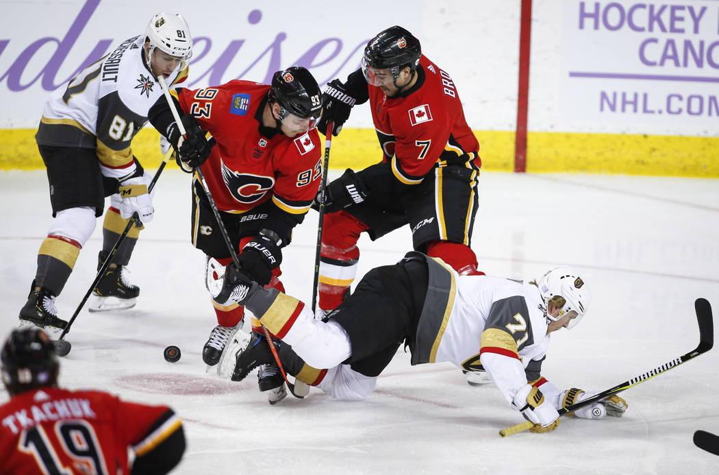William Karlsson de los Vegas Golden Knights, a la derecha, es derribado mientras su compañero de equipo, Jonathan Marchessault, a la izquierda, y Sam Bennett de los Calgary Flames y T.J. Brodie ...