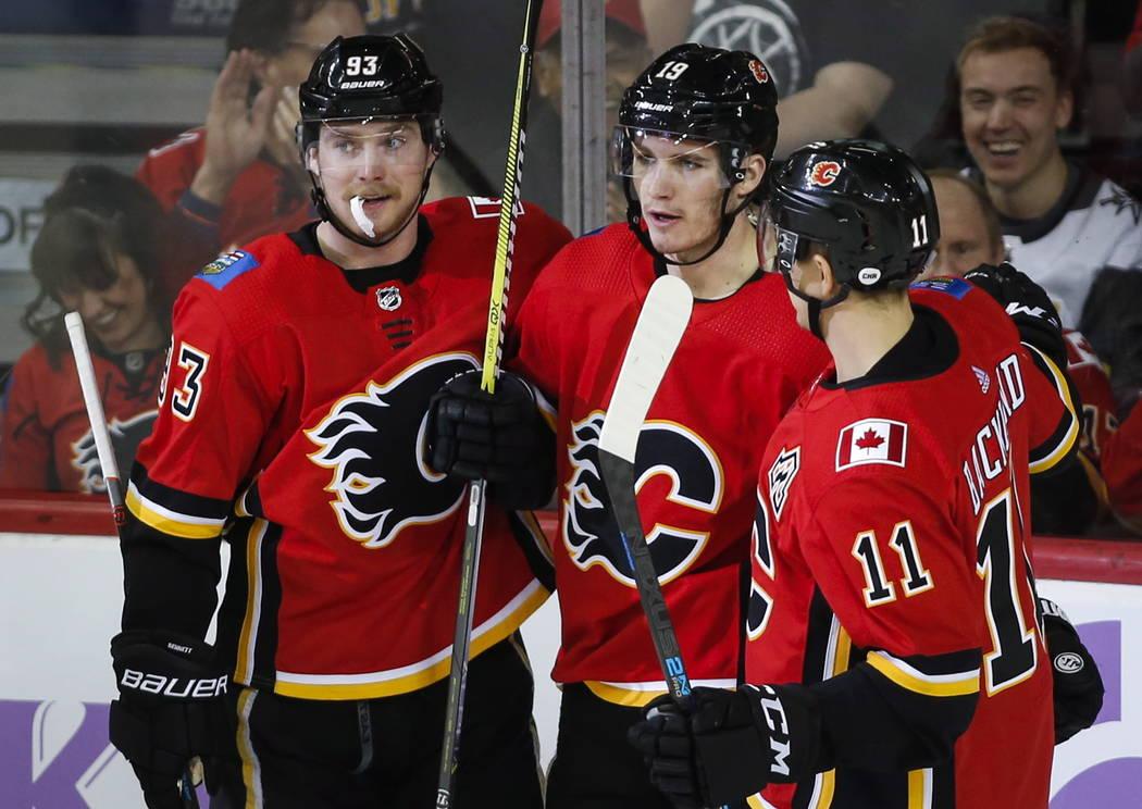 Matthew Tkachuk, centro de los Calgary Flames, celebra su gol con sus compañeros Sam Bennett, a la izquierda, y Mikael Backlund, de Suecia, durante el segundo juego de hockey de la NHL contra los ...