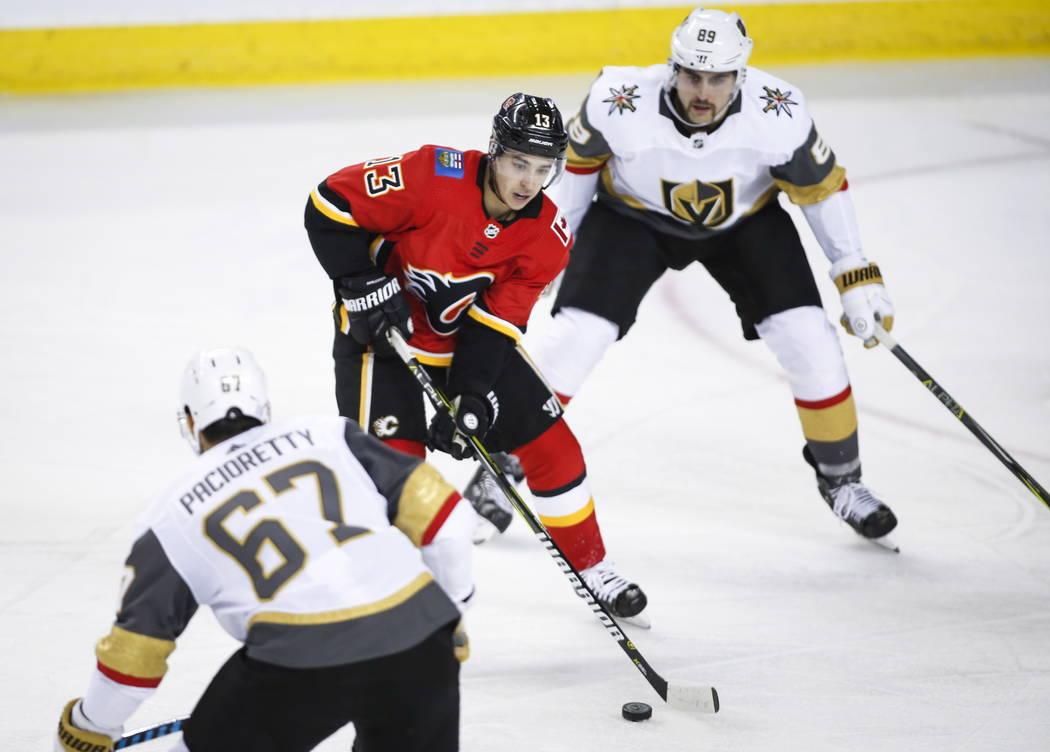 Johnny Gaudreau de los Calgary Flames, centro, patina entre Max Pacioretty, izquierda, y Alex Tuch de los Vegas Golden Knights durante el segundo tiempo de acción de hockey de la NHL en Calgary, ...