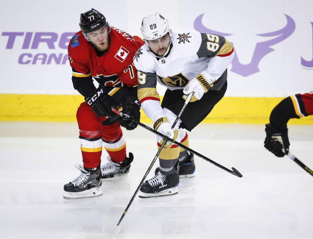 Alex Tuch de Vegas Golden Knights, a la derecha, y Mark Jankowski, de Calgary Flames, luchan por su posición durante el tercer tiempo de acción de hockey de la NHL en Calgary, Alberta, lunes 19 ...
