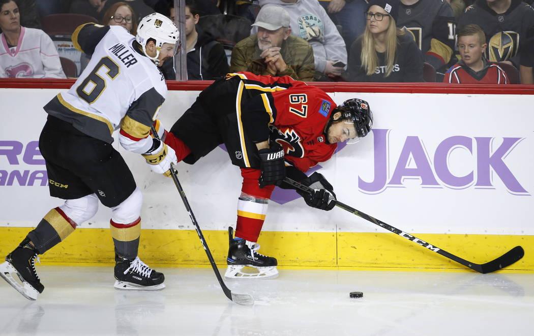 Colin Miller de los Golden Knights de Vegas, a la izquierda, avienta a Michael Frolik, de la República Checa, de los Calgary Flames, a los tableros durante el tercer tiempo de un juego de hockey ...