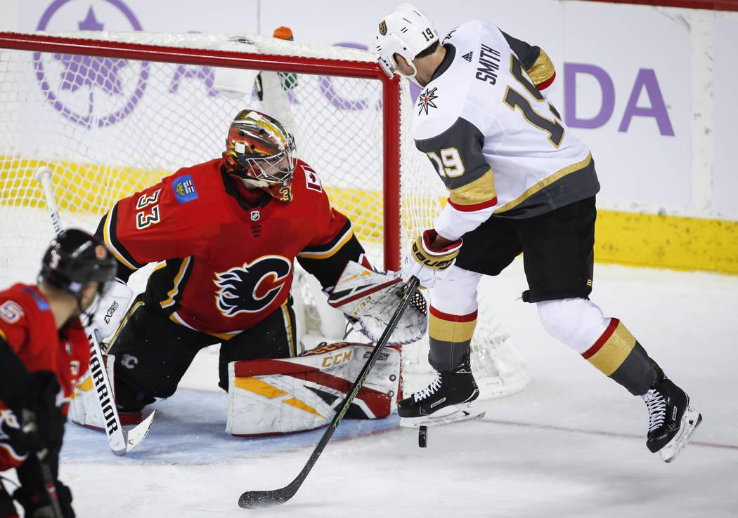 David Rittich, de los Calgary Flames, bloquea el disparo de Reilly Smith de los Vegas Golden Knights, a la derecha, durante el tercer tiempo de un juego de hockey de la NHL en Calgary, Alberta, el ...