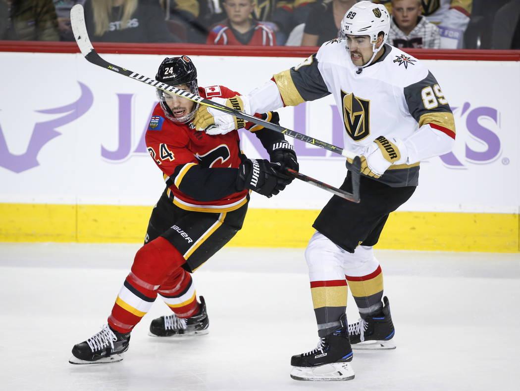 Alex Tuch, de los Golden Knights de Las Vegas, a la derecha, controla a Travis Hamonic de los Calgary Flames durante el primer período del juego de hockey de la NHL en Calgary, Alberta, el lunes ...